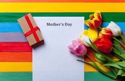 Bunch of tulips, gift and sheet of the paper lying on the table royalty free stock photography