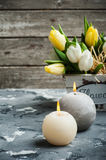Bunch of tulips and lit candles Stock Photo