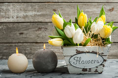 Bunch of tulips and lit candles. White and yellow tulips and lit candles on concrete background. Spring in the garden background Royalty Free Stock Photos