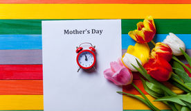 Bunch of tulips, little red clock and sheet of the paper lying o Royalty Free Stock Image