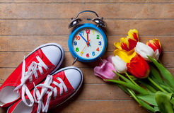 Bunch of tulips, red gumshoes and clock lying on the table Royalty Free Stock Image