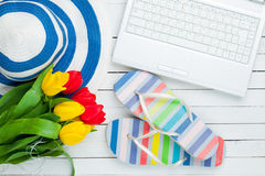 Bunch of tulips, sandals, hat and laptop on the wonderful white Royalty Free Stock Images