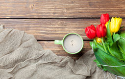 Bunch of tulips, scarf and cup of coffee on the wonderful brown Royalty Free Stock Images