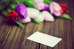Bunch of tulips and white card. On wooden table Royalty Free Stock Images