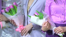 Bunch of tulips in woman`s hands. Winners success. Award ceremony of female woman of beauty contest on stage, victory