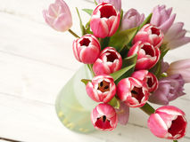 Bunch of tulips on wood. Beautiful bunch of tulips on a rustic white barn wood background Royalty Free Stock Images