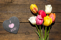 Bunch of tulips on a wooden background, slate with word i love y Stock Image