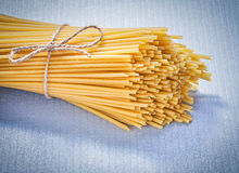 Bunch of uncooked spaghetti on blue background food and drink co. Ncept Stock Photo