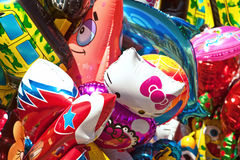 Bunch of various cartoon characters balloons at fair. Khabarovsk, Russia - May 1, 2017: Hello Kitty, Patrick Star and other colorful fun balloons background stock photos