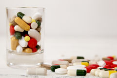 Bunch of various color pills in glass on white table Stock Photos