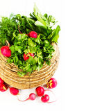 A bunch of vegetables in wicker basket. A bunch of fresh different vegetables in a bowl wicker basket on white wooden background Stock Photos