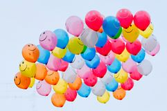 Bunch of vibrant color balloons with smiley face in the sky, Pune stock photography