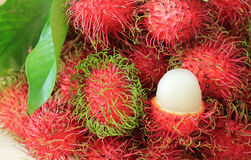 Bunch of Vibrant Color Ripe Rambutan Whole Fruits and Opened to Show Delectable Juicy White Meat Stock Photos