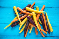 Bunch of vibrant rainbow carrots on blue wooden table Stock Photo