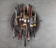 A bunch of vintage cutlery in a copper plate. On a concrete background Stock Photos