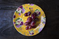 Bunch of washed ripe and juicy red grapes on vine isolated on an ornate yellow plate positioned against a wooden table. Horizontal shot of plate with fresh fruit royalty free stock images