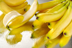 A bunch of wet bananas. On a mirror royalty free stock photo