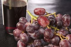 Cluster of wet red grapes and wine Stock Image