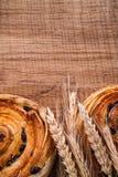 Bunch of wheat ears raisin bakery on oaken wooden Royalty Free Stock Image