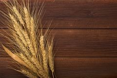 Bunch of wheat ears on the wooden table. Sheaf of wheat over wood background. Harvest concept stock photography