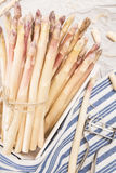 Bunch of white asparagus in box, on crumpled paper with metallic peeler Stock Photo