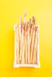 Bunch of white asparagus spears in a box, on vivid yellow Royalty Free Stock Photo