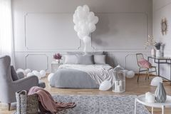 Bunch of balloons above king size bed with grey pillows and duvet in elegant bedroom with golden chair with pink pillow and. Bunch of white balloons above king royalty free stock photo