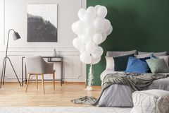 Bunch of balloons in elegant grey and green bedroom interior with king size bed with grey bedding, blue pillows and moss. Bunch of white balloons in elegant grey stock photos