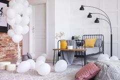 Bunch of white balloons in bedroom with single metal bed and lamp. Bunch of white balloons in stylish bedroom interior with single metal bed and lamp stock photo