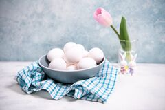 A bunch of white chicken eggs in a blue bowl. Farm product. Nearby are pink tulip. White and blue pastel background. Preparing for