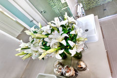 Bunch of white flowers and buds against to the mirror on the gray color workshop near to the sink in the modern washroom. White flowers and a modern washstand stock image