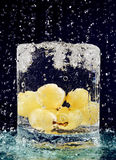 Bunch of white grapes falling down in water glass Stock Images