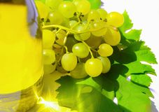 A bunch of white grapes  near the bottle of wine. A bunch of white grapes with a green leaf near the bottle of wine, which reflects the light glare. Top view stock photography