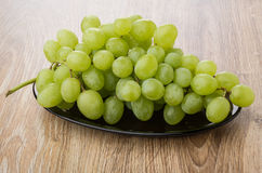 Bunch of white grapes in oval dish on table Royalty Free Stock Images
