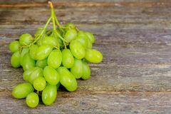 Bunch of white grapes on a wooden table. Fresh bunch of white grapes on a wooden table royalty free stock photo