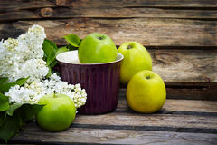 A bunch of white  lilac and green apples on old wooden backgroun Royalty Free Stock Photos