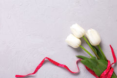 Bunch of white tulips flowers with  red  ribbon on  grey texture Royalty Free Stock Photography