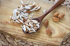 A bunch of whole and chopped almond nuts on a wooden board and in a wooden oak spoon on the table. stock photo