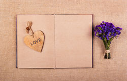 A bunch of wildflowers, an open book with empty pages and a wooden heart. Romantic concept. Backgrounds and textures. Stock Photos