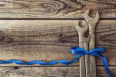 Bunch of wrenches with a blue ribbon on a rustic wooden backgrou Stock Images