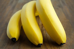Bunch of yellow bananas lie on a wooden background Royalty Free Stock Image
