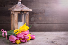 Bunch  yellow and pink spring tulips  and candle in lantern on v Stock Photo