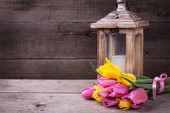 Bunch  yellow and pink spring tulips  and candle in lantern on v Stock Images