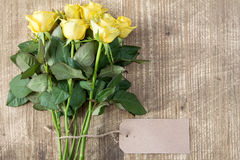 Bunch of yellow roses with blank tag Stock Photo
