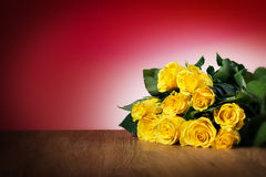 Bunch of yellow roses. On a table and with red background, free space Royalty Free Stock Photo
