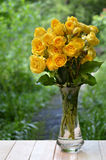 Bunch of yellow roses in a vase. In the garden. Beautiful bouquet of fresh yellow garden roses on a wooden background in a garden. Exquisite product of nature Royalty Free Stock Photography