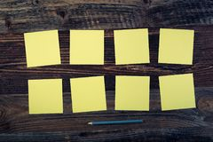 Sticky notes. Bunch of yellow sticky notes on the wooden background royalty free stock images