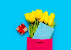 Bunch of yellow tulips and blue envelope in cool shopping bag an Royalty Free Stock Image