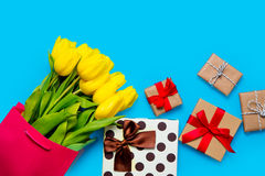 Bunch of yellow tulips in cool shopping bag and cute gifts on th Stock Images