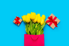 Bunch of yellow tulips in cool shopping bag and cute gifts on th Stock Image